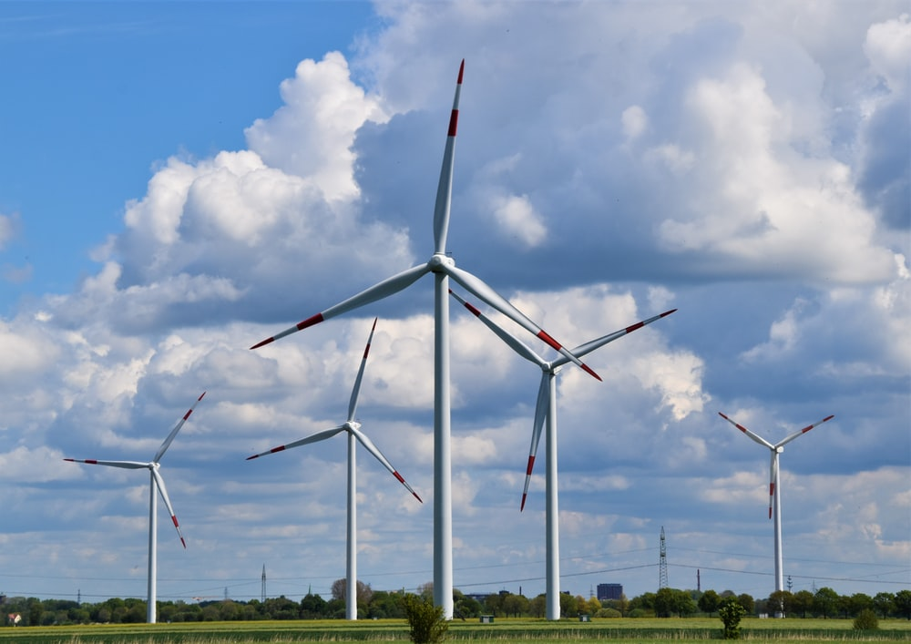 white wind turbines on green grass field under blue and white cloudy sky during daytime