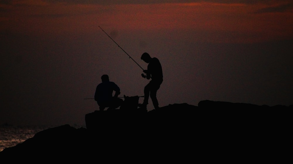 silhouette of 3 person on rock during sunset