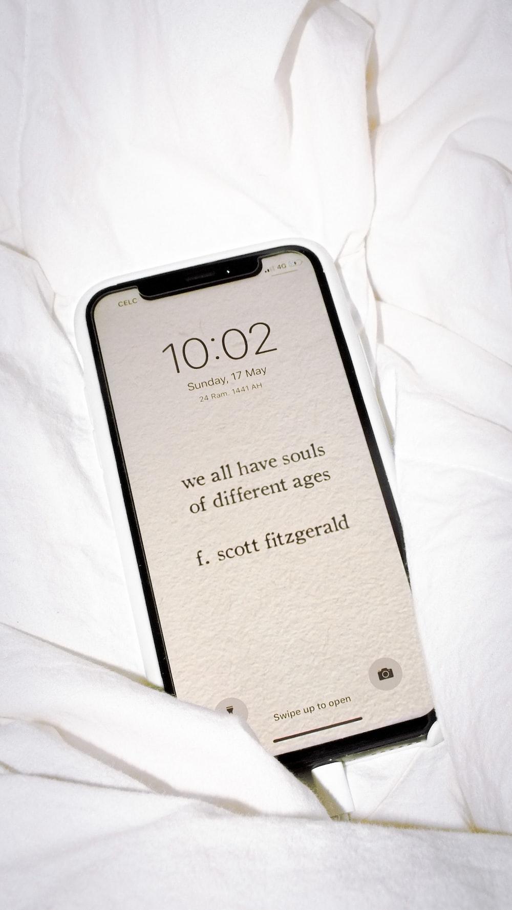 black samsung galaxy smartphone on white textile