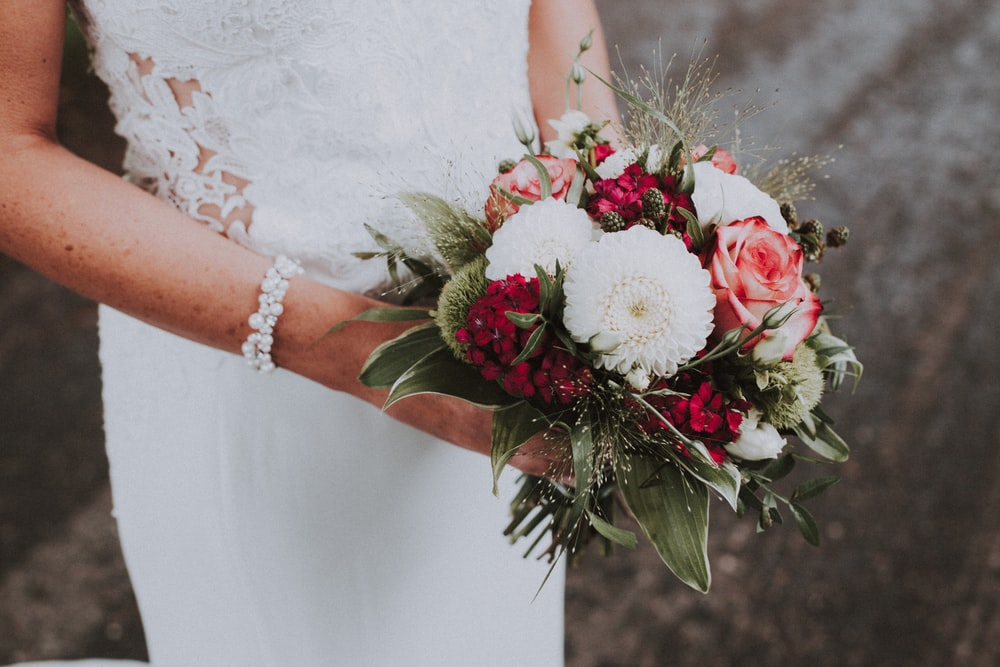 woman holding white and pink flowers