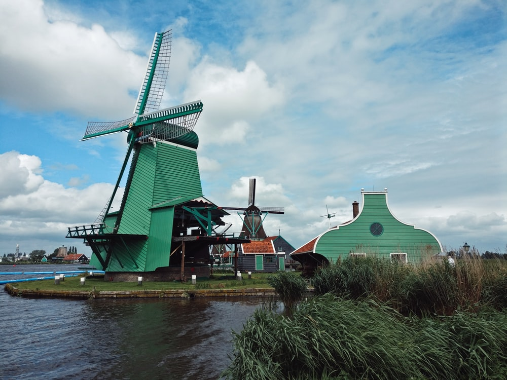 green and brown windmill beside river during daytime