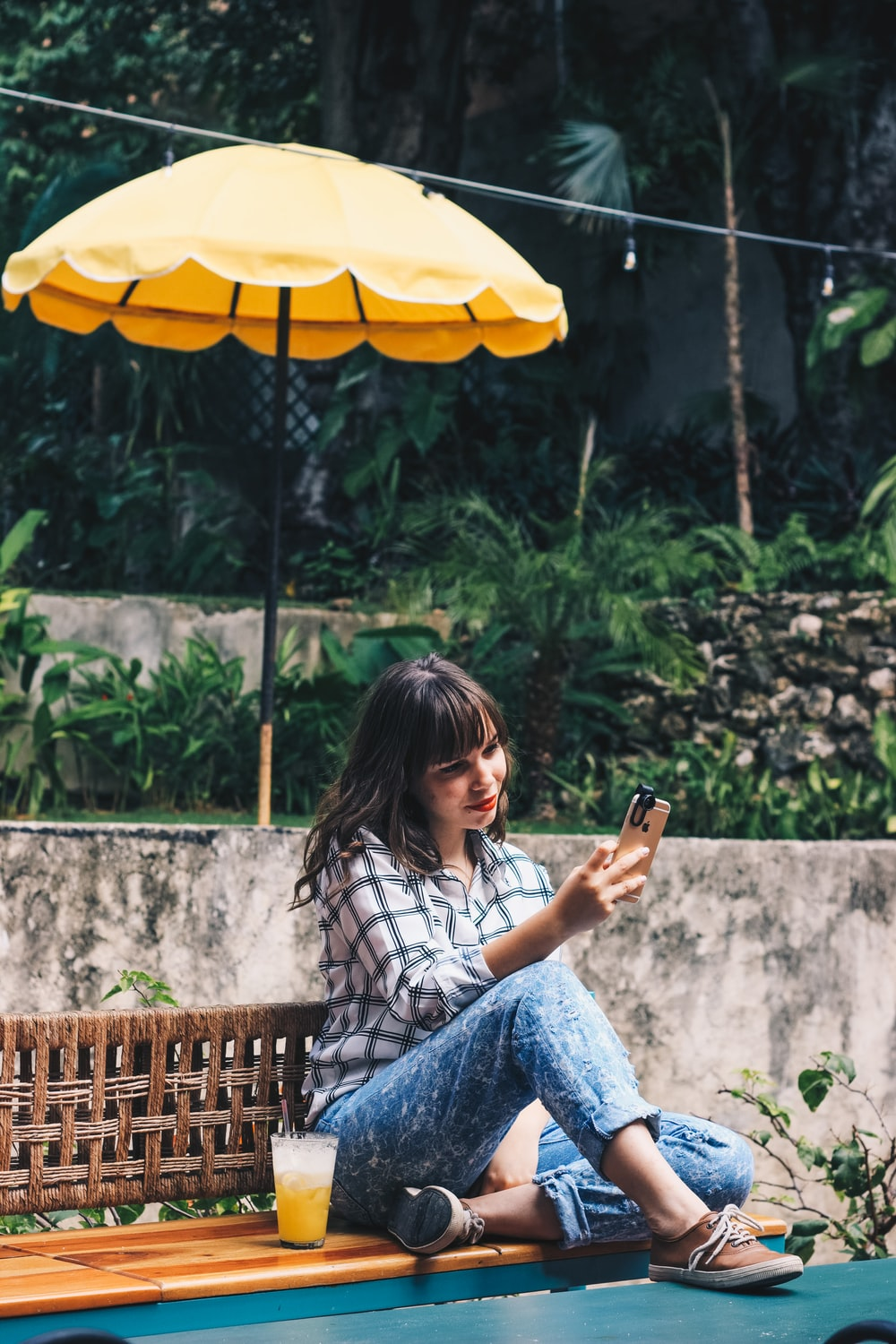 woman in blue denim jeans sitting on brown wooden bench holding smartphone