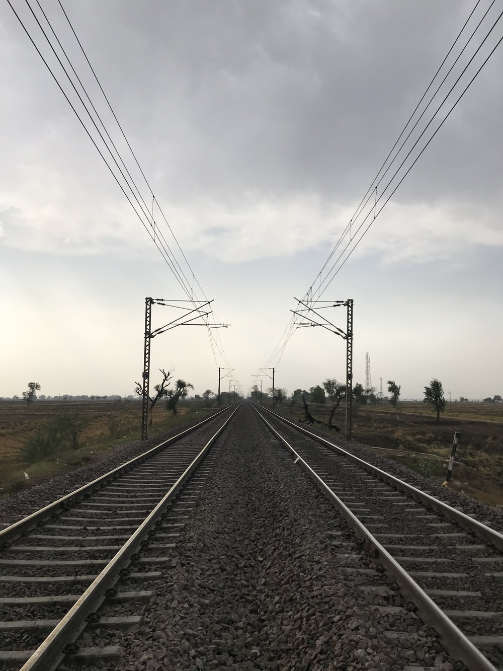 black metal train rail under white clouds during daytime