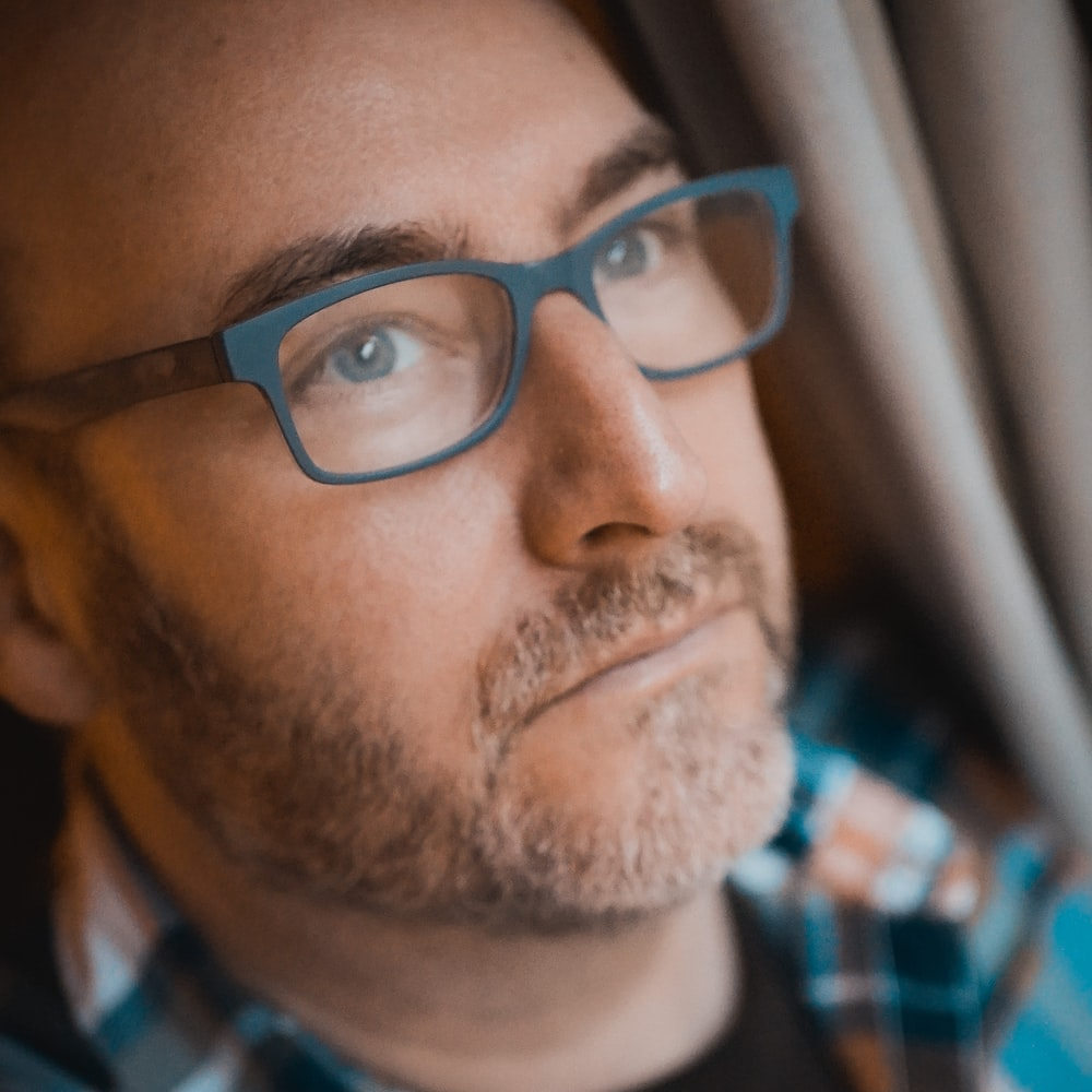 man in blue white and red plaid shirt wearing black framed eyeglasses