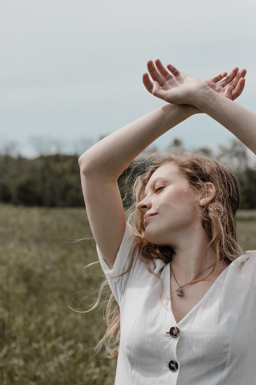 woman in white sleeveless shirt raising her hands