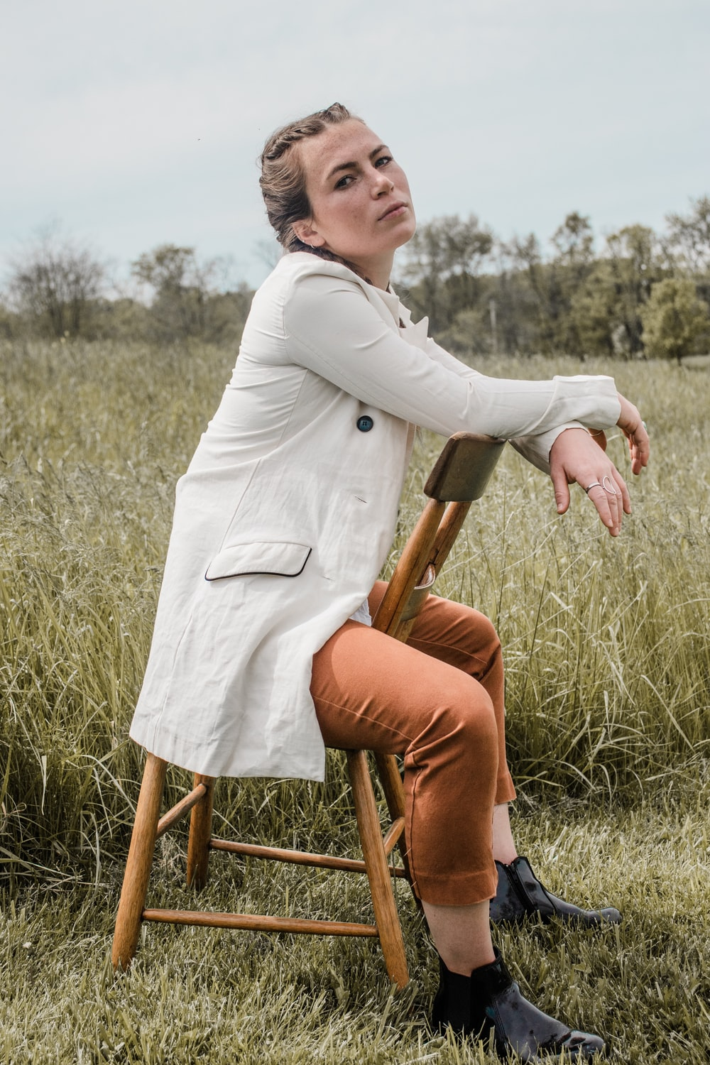 woman in white long sleeve shirt and brown pants sitting on brown wooden seat