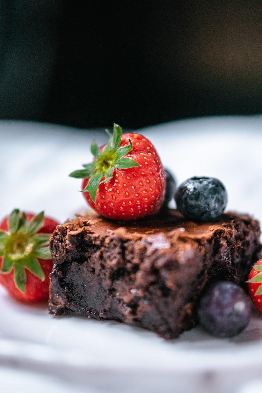 strawberry on chocolate cake on white ceramic plate