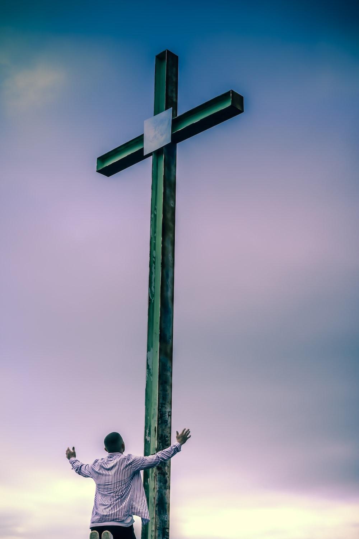 black wooden cross under gray sky