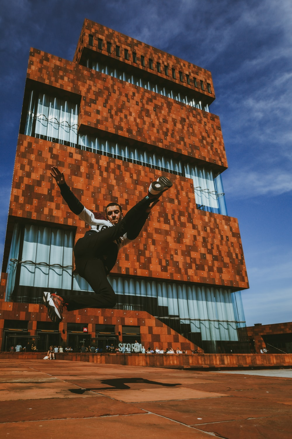 man in black jacket and black pants jumping on brown building during daytime