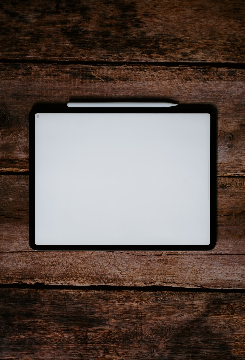 white and black tablet computer on brown wooden table