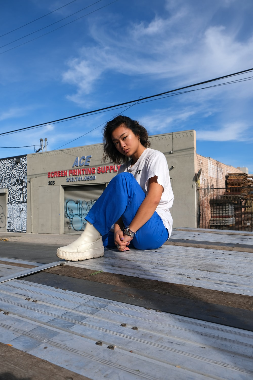 woman in white t-shirt and blue denim jeans sitting on wooden floor
