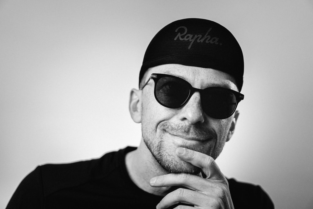 man in black crew neck shirt wearing black and white fitted cap and black sunglasses