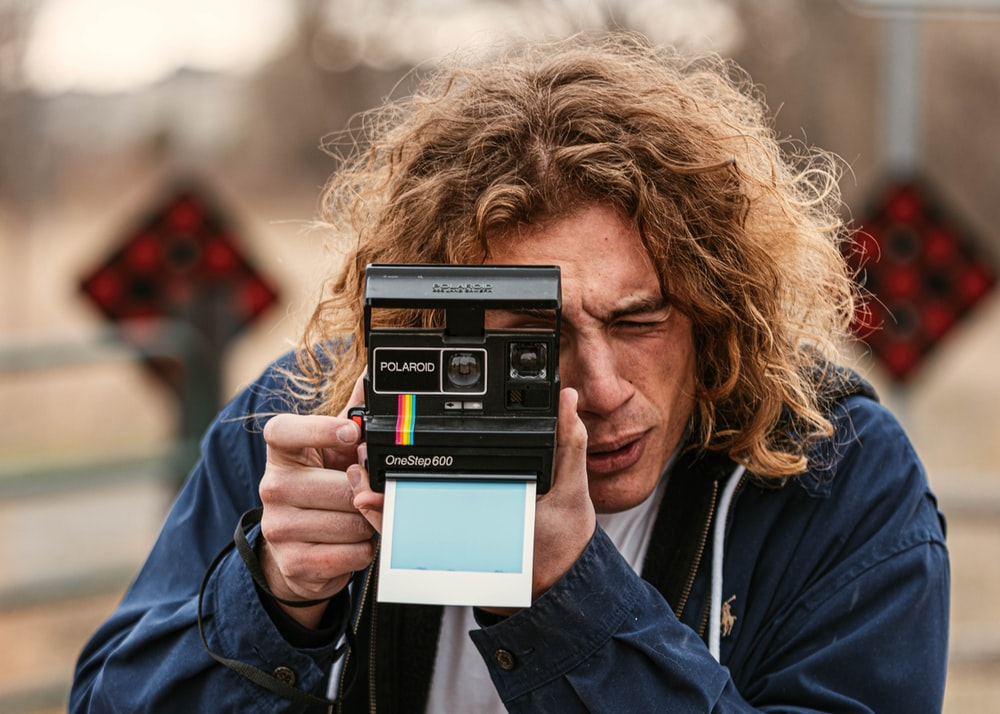 woman in blue jacket holding black and white digital camera