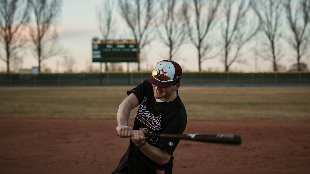 man in black t-shirt playing baseball during daytime