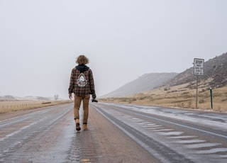 woman in brown and black plaid coat walking on gray asphalt road during daytime