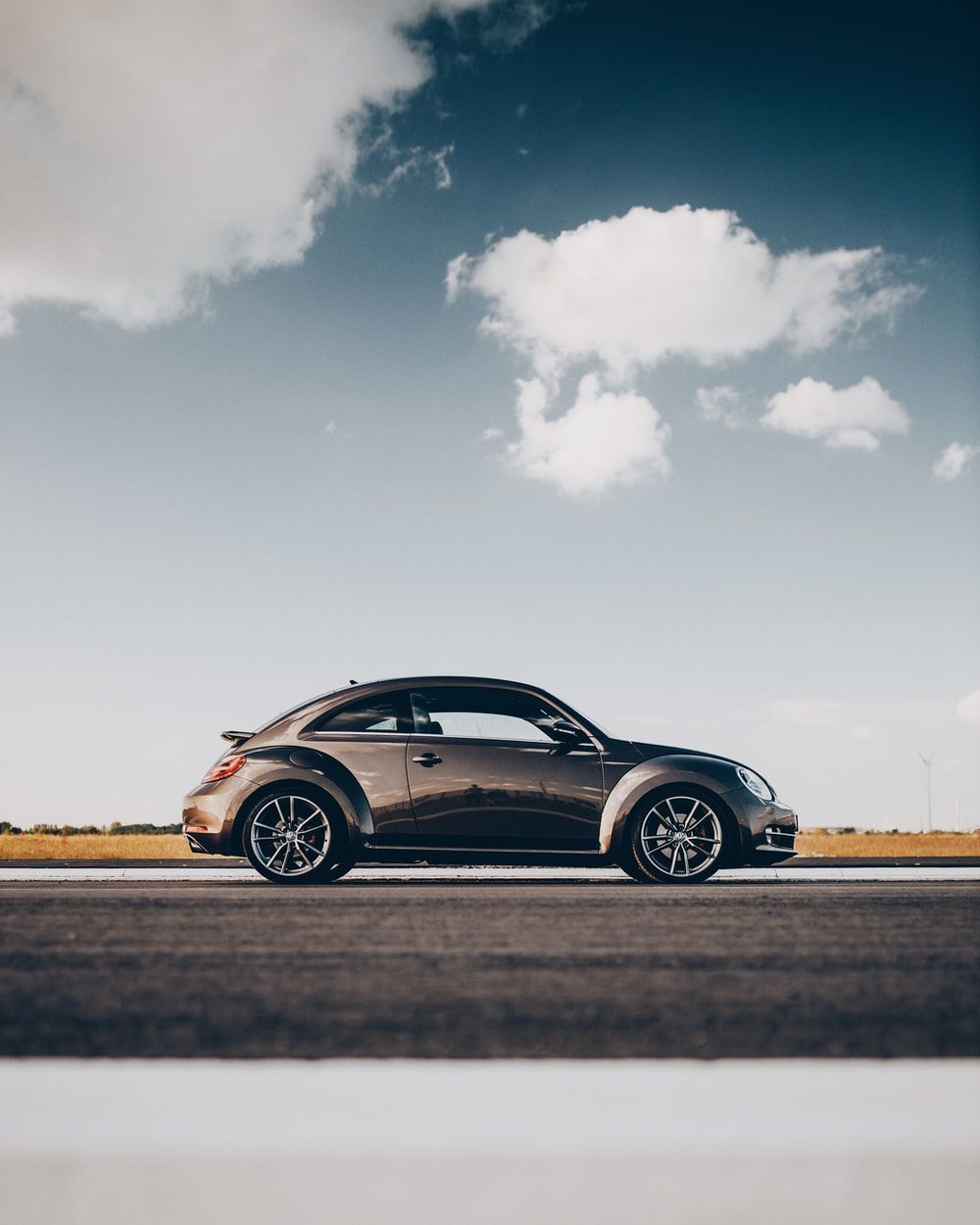 black coupe on brown field under white clouds and blue sky during daytime