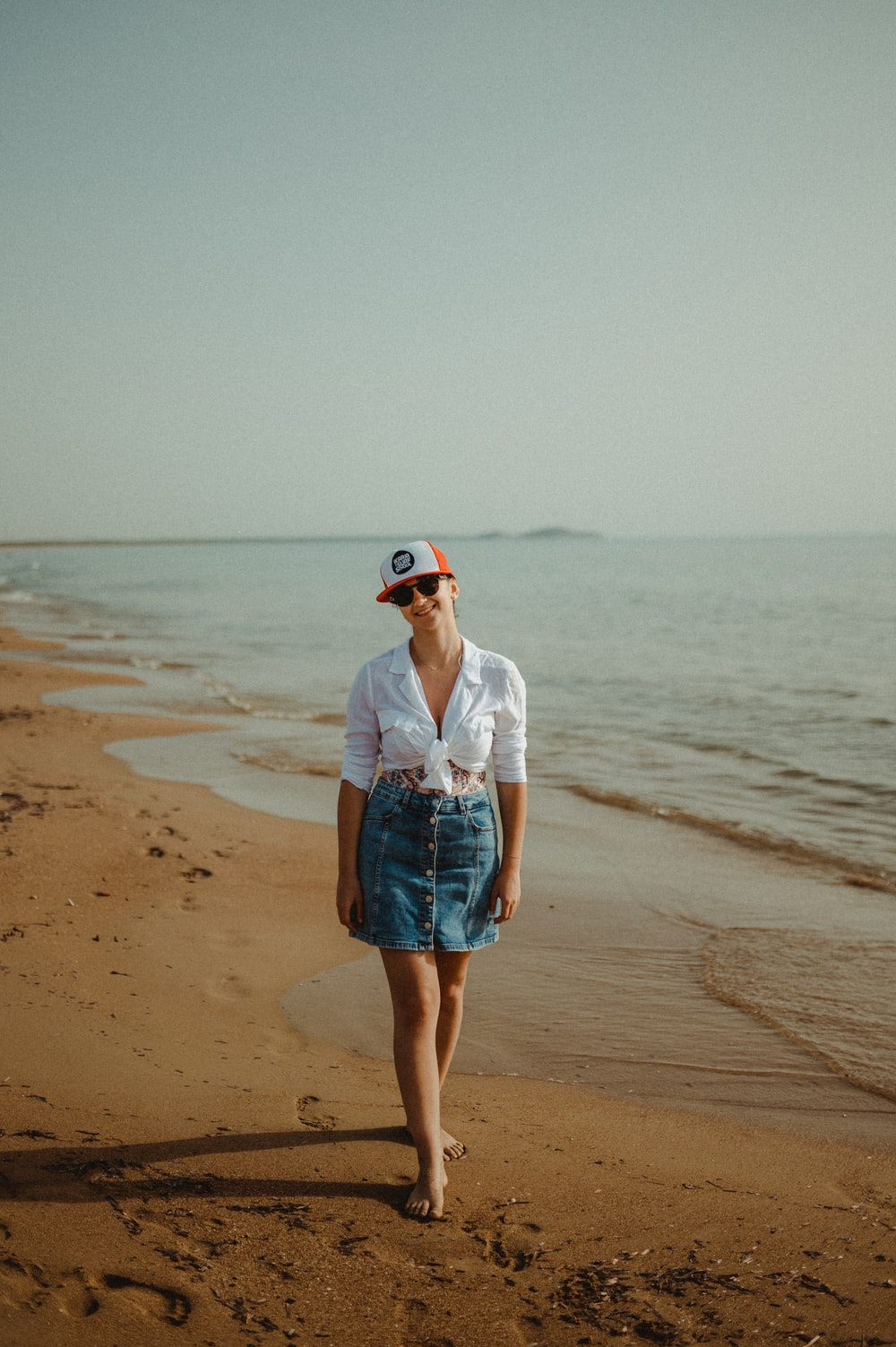 woman in white shirt and blue denim shorts standing on beach during daytime