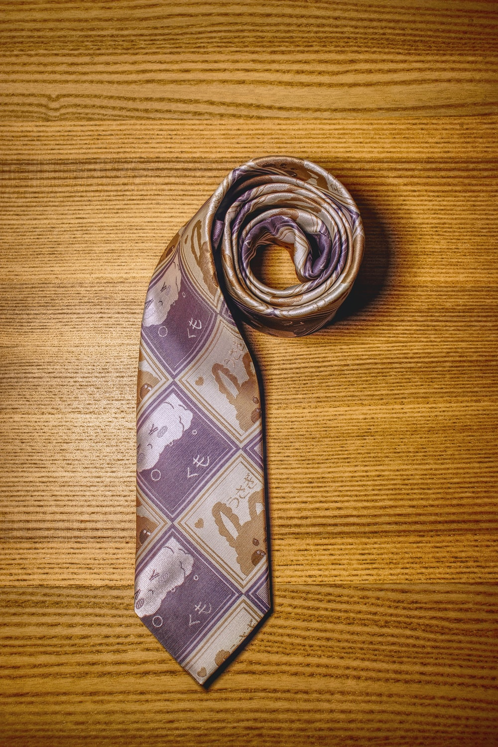 brown and white necktie on brown wooden table