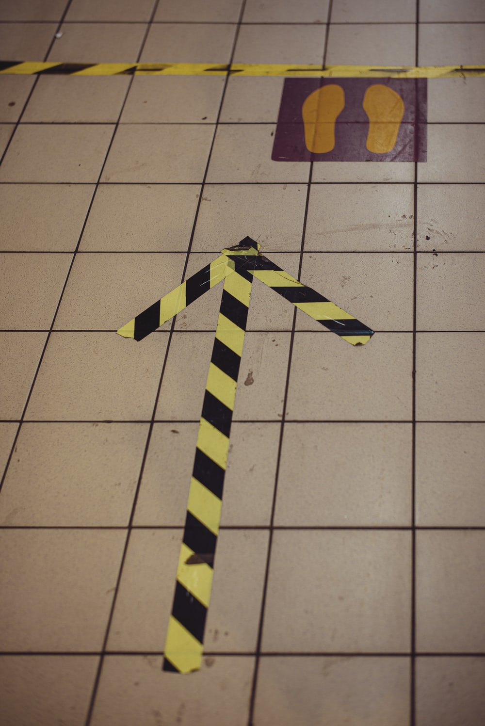 yellow and black cross on white floor tiles