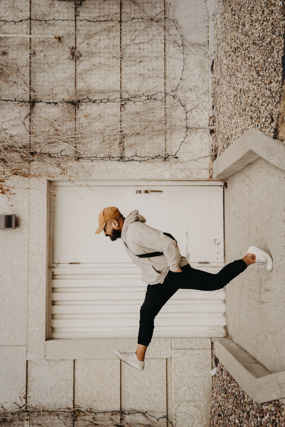 man in white long sleeve shirt and black pants jumping on white concrete wall during daytime