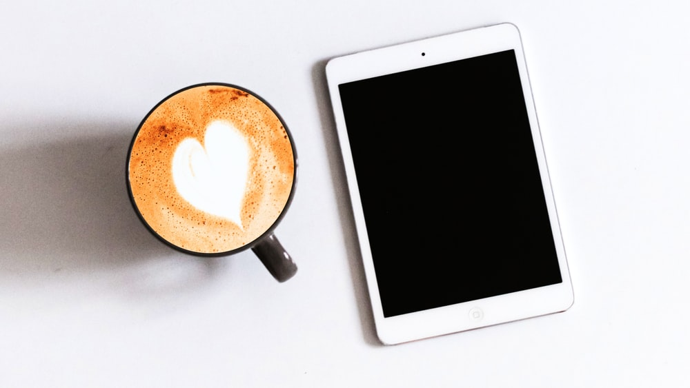 white ipad beside black ceramic mug with brown liquid