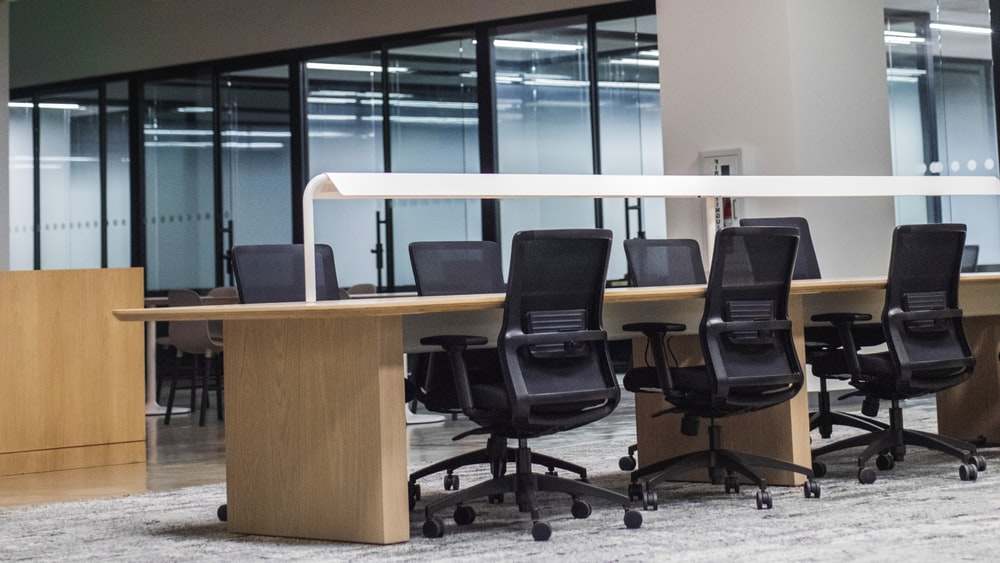 black office rolling chair beside brown wooden desk