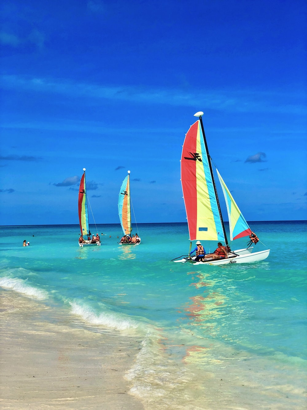 people riding on sail boat on sea during daytime