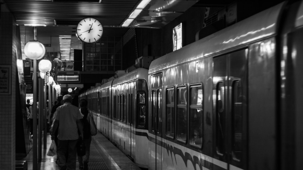 grayscale photo of man in black jacket standing beside train