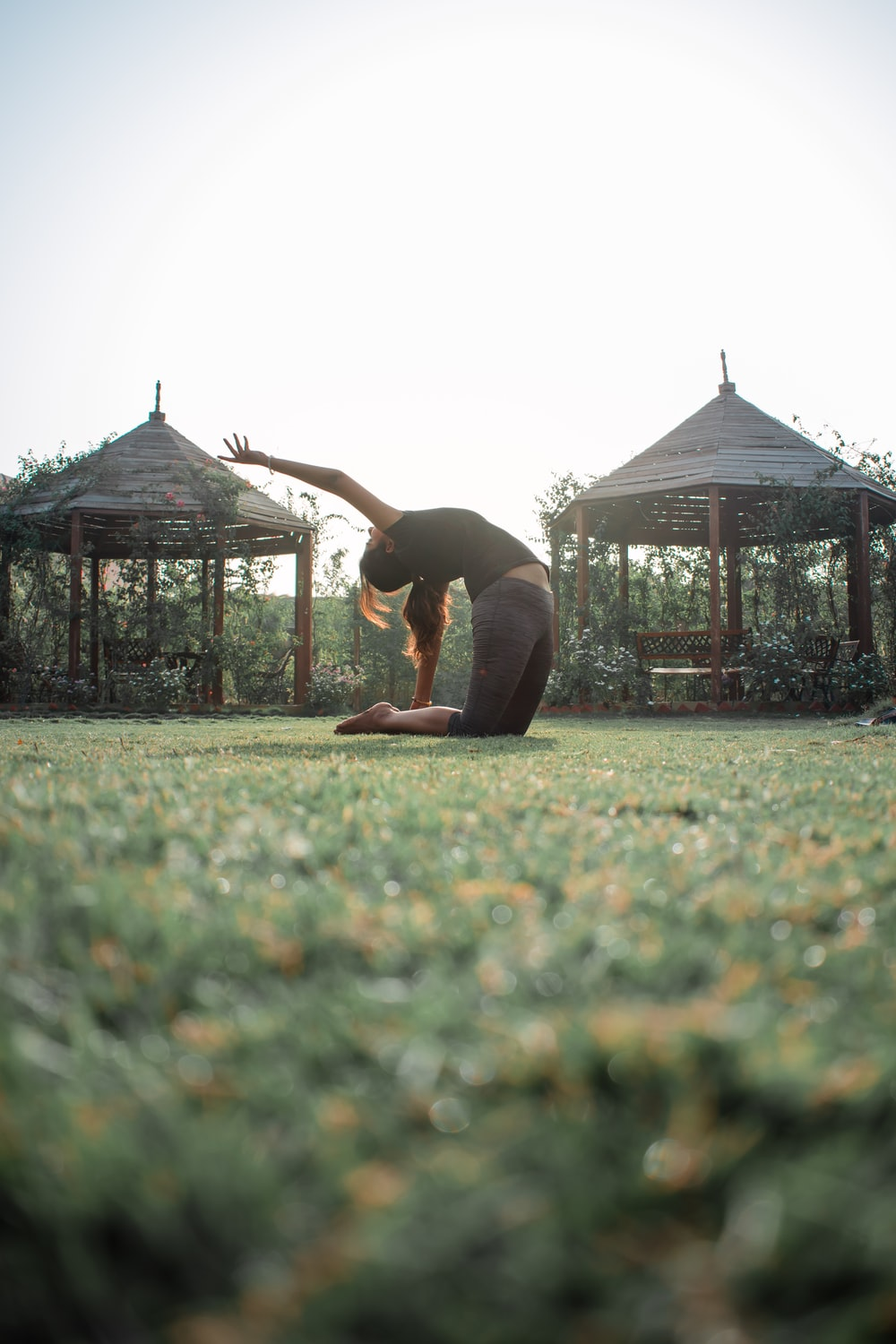 woman in black tank top and black pants doing yoga on green grass field during daytime