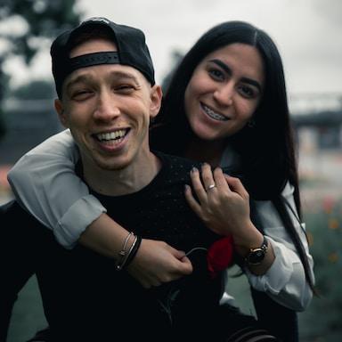 man in black long sleeve shirt smiling beside woman in white long sleeve shirt
