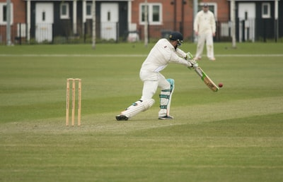 man in white baseball jersey playing golf during daytime cricket teams background