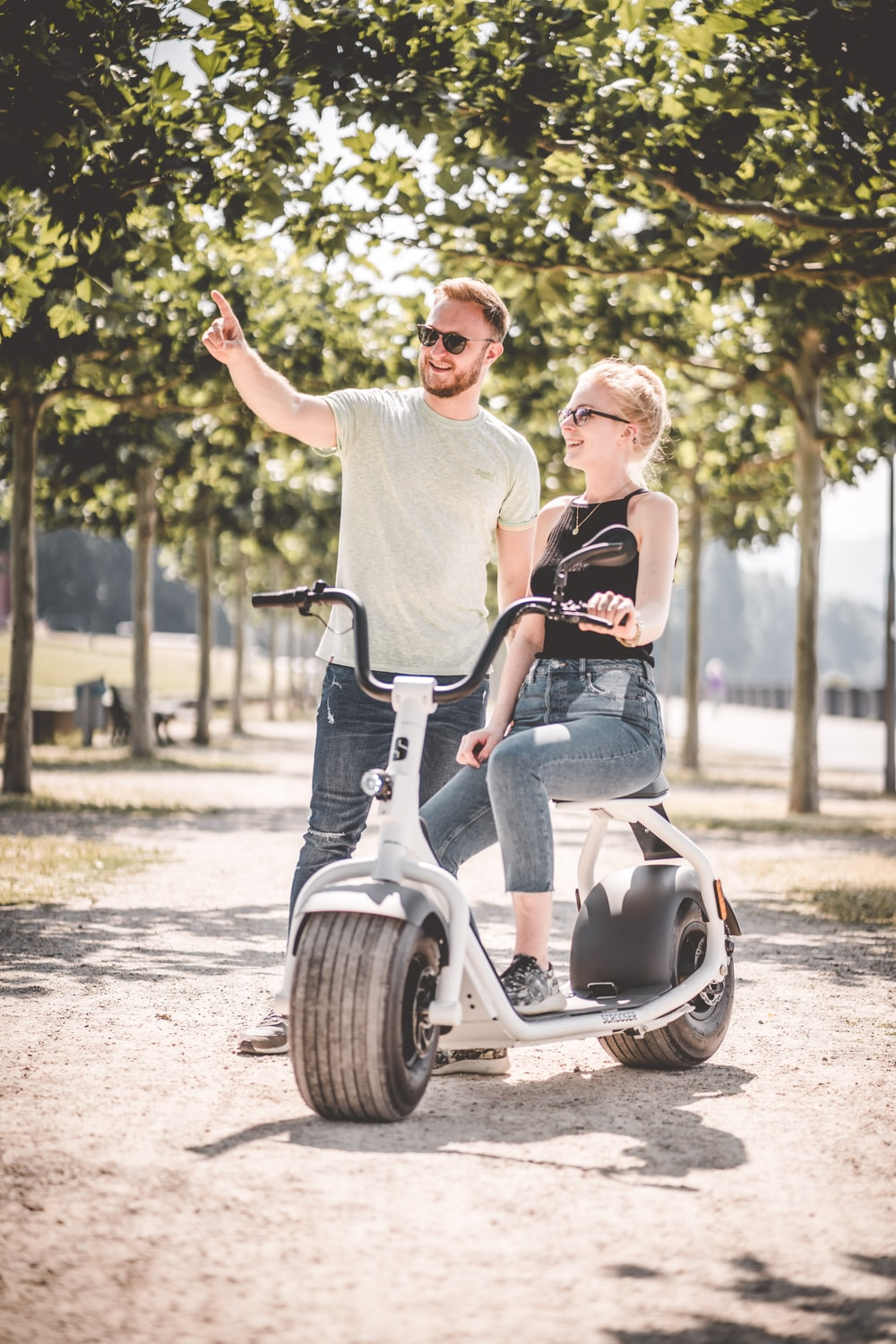 man and woman riding on motorcycle during daytime
