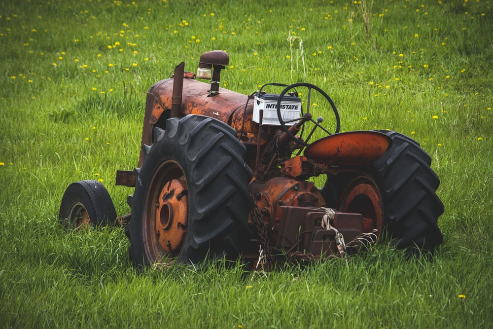 orange and black tractor on green grass field during daytime