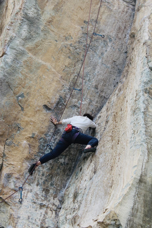 man in white shirt and black pants climbing on brown rock during daytime