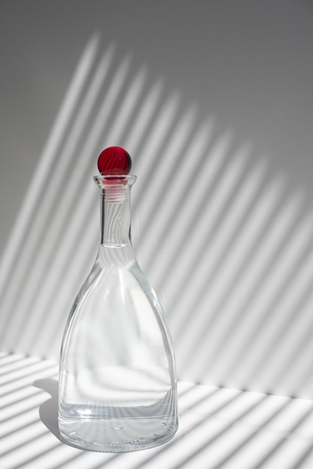 clear glass bottle with red lid