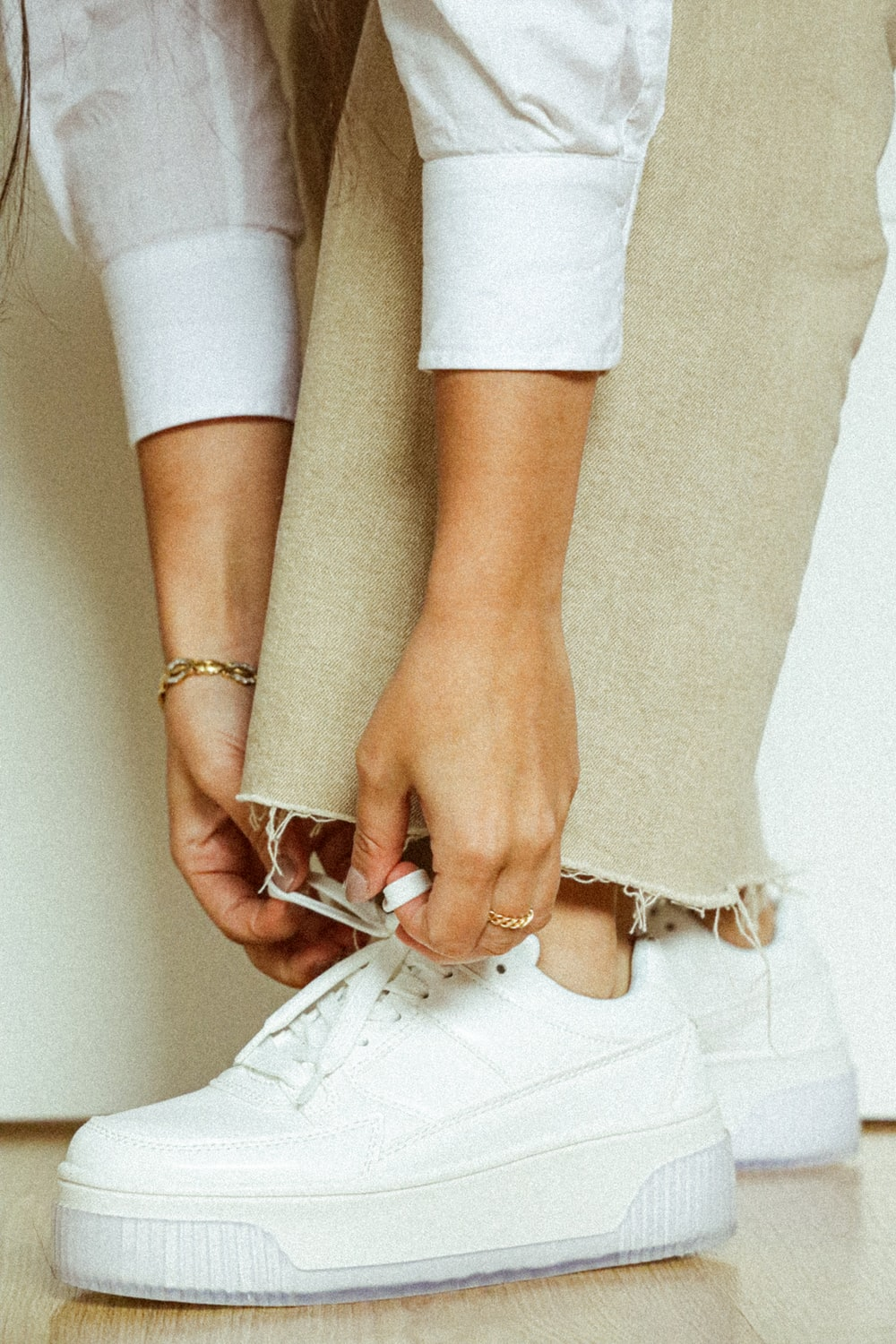woman in white pants wearing silver and gold bracelet