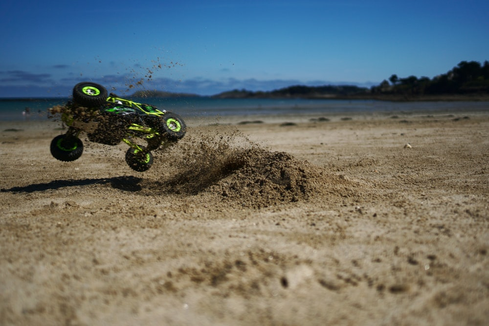 green and black motocross dirt bike on brown sand during daytime