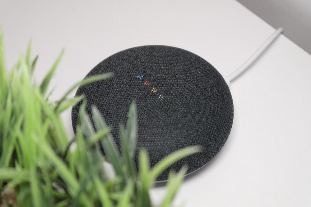 black round portable speaker on white table