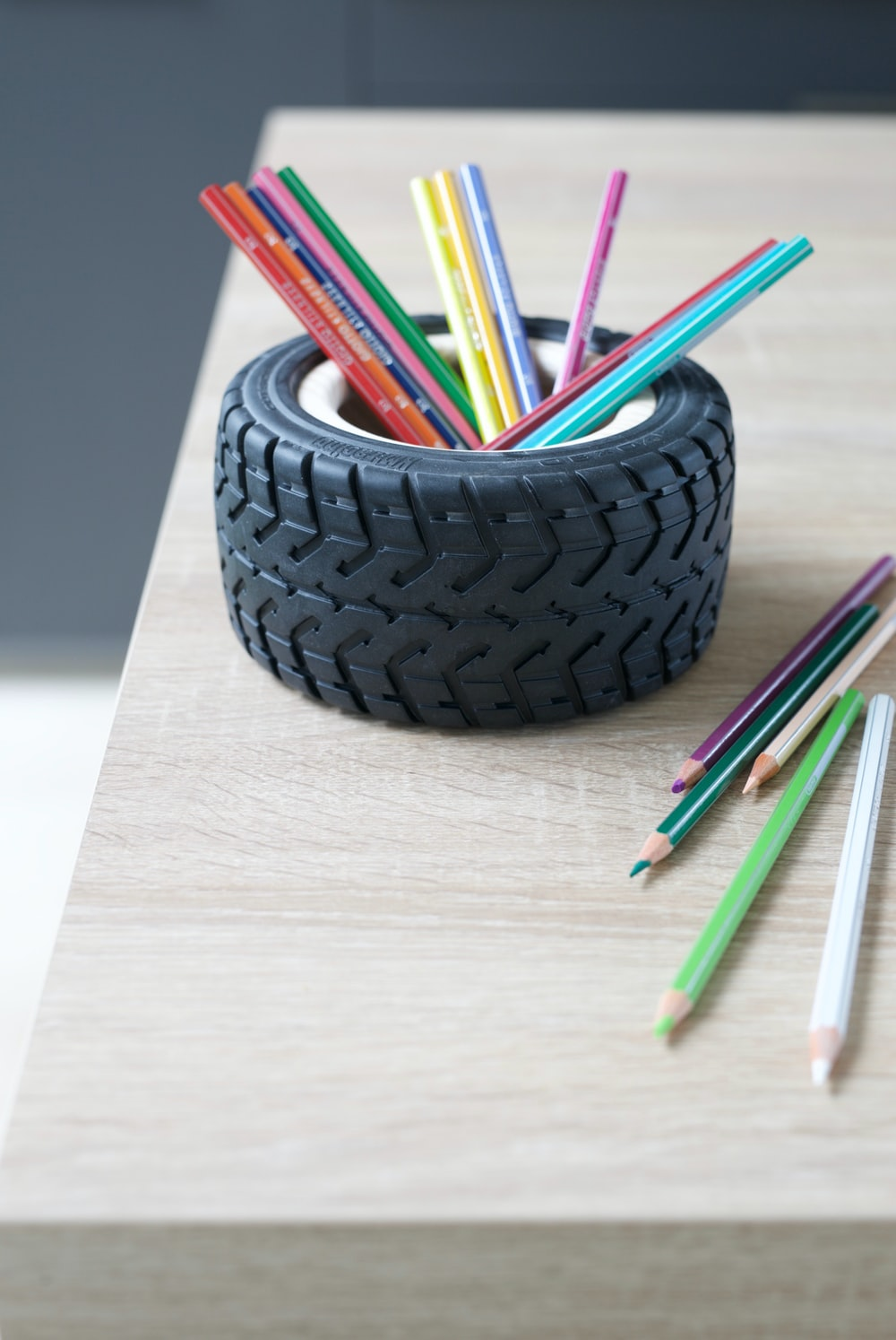 assorted color pencils on black round container