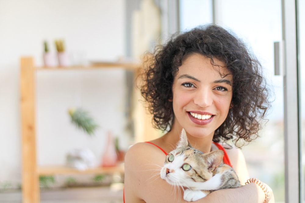 smiling woman with brown and white cat on her shoulder
