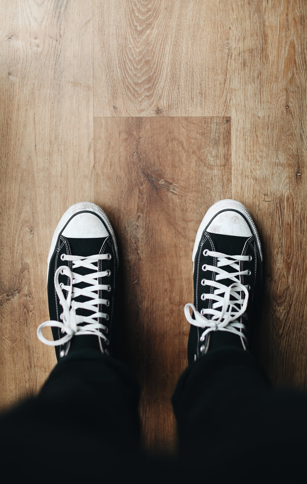 person wearing black and white converse all star sneakers