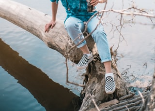 woman in blue shirt and white and black pants sitting on brown tree trunk during daytime