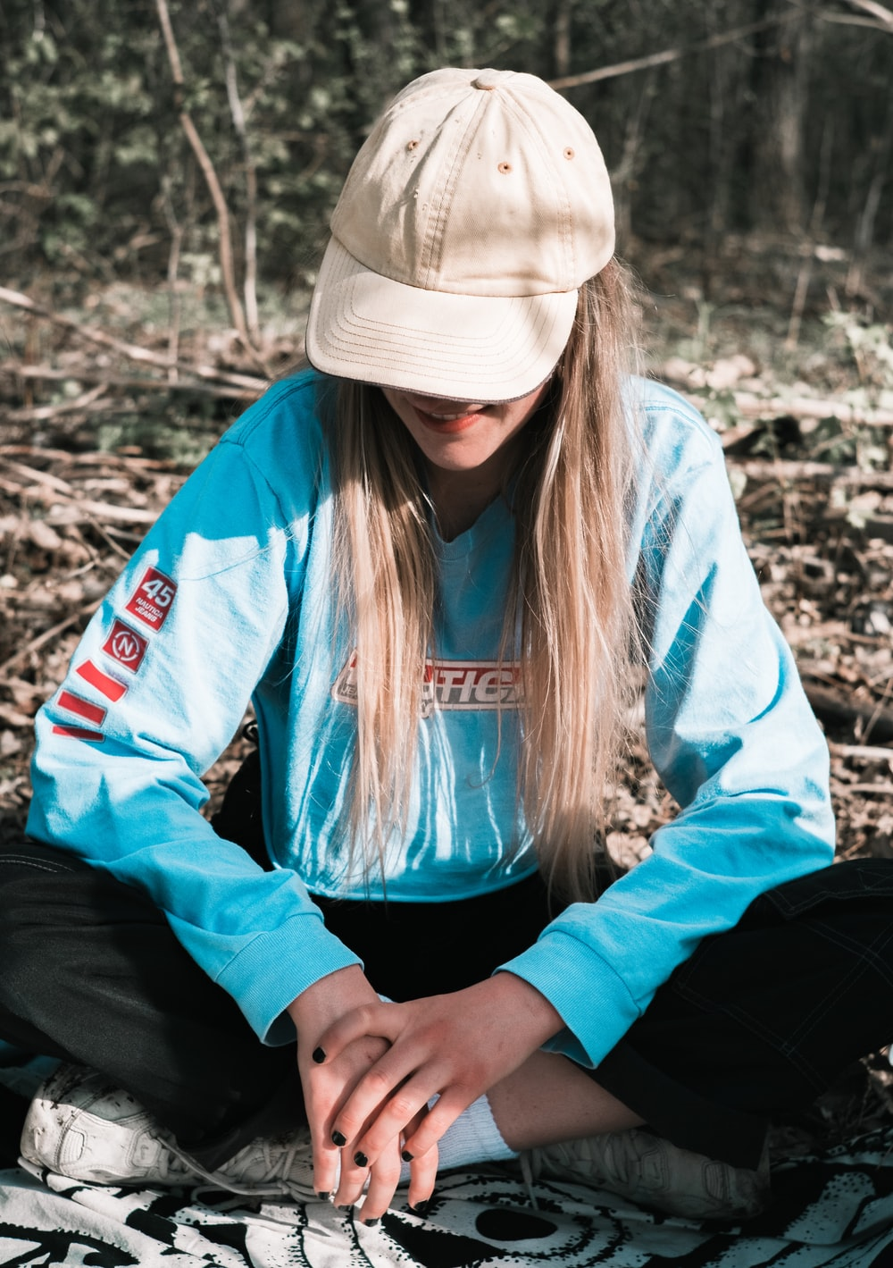 woman in blue jacket and white knit cap sitting on ground