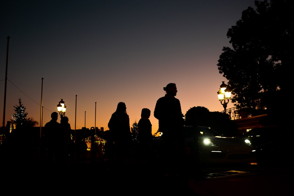 silhouette of people standing on road during sunset
