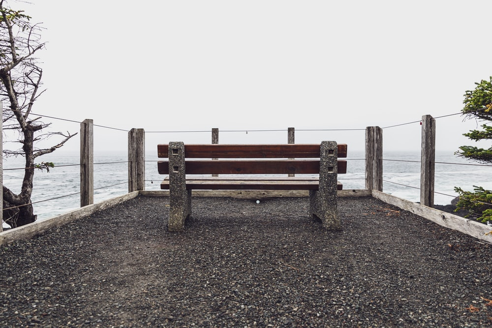 brown wooden bench on brown sand near body of water during daytime