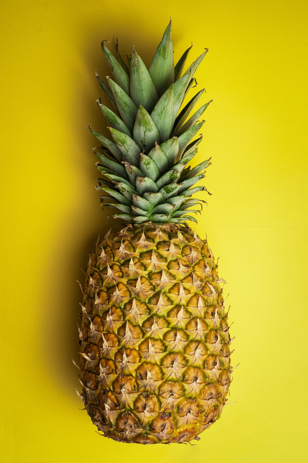 pineapple fruit on yellow surface