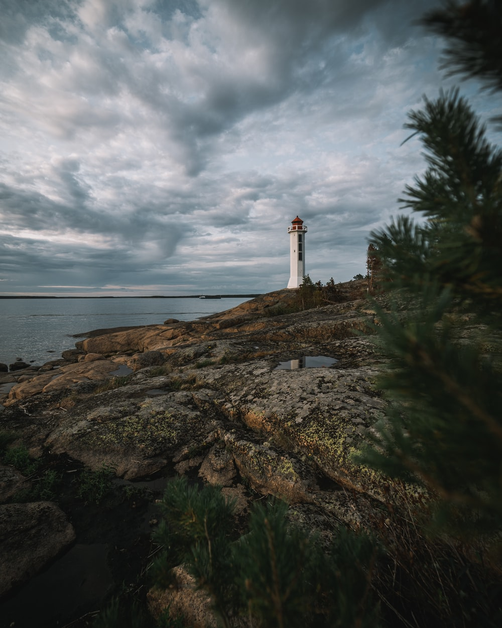 white and brown lighthouse on brown rock formation near body of water under white clouds during