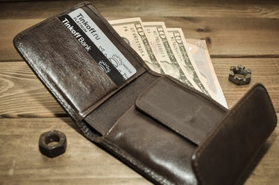 brown leather bifold wallet on brown wooden table