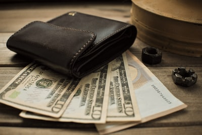 brown leather bifold wallet on white newspaper