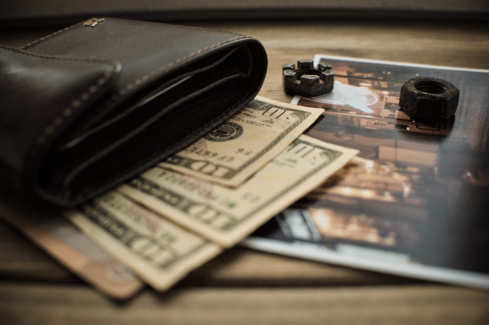 black leather bifold wallet on banknotes